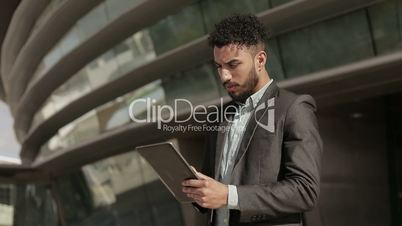 Serious confident man wearing formal wear holding tablet