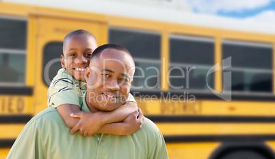 African American Man and Child Piggyback Near School Bus