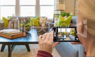 Woman Taking Pictures of A Living Room in Model Home with Her Sm