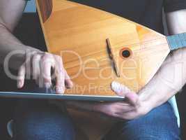 Musician with a balalaika and tablet computer