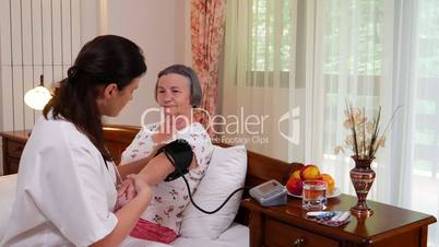 Family doctor checking senior woman using stethoscope at home