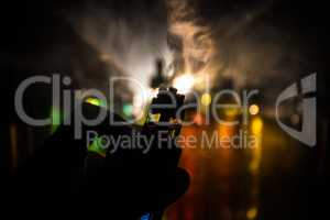 Vape concept. Electronic Cigarette vape explosion. Smoke clouds and vape liquid bottles on dark background. Light effects. Useful as vape advertisement.
