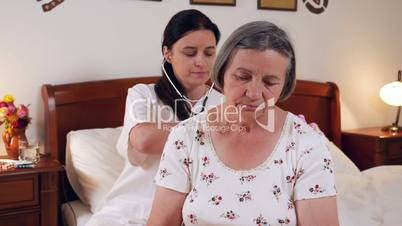 Doctor checking senior woman lungs with stethoscope at home