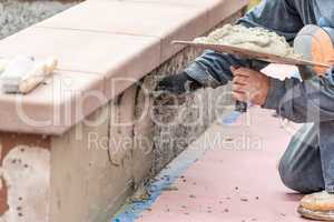 Tile Worker Applying Cement with Trowel at Pool Construction Site