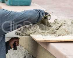 Tile Worker Mixing Wet Cement On Board At Pool Construction Site