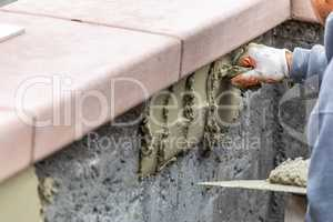 Tile Worker Applying Cement with Trowel at Pool Construction Sit