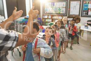 School kids standing and forming a queue in classroom at school