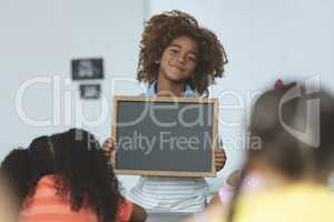 African ethnicity schoolboy holding a slate and looking at camera in classroom