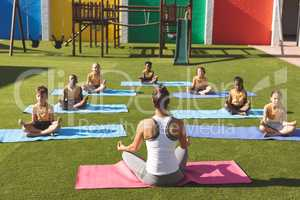 Trainer teaching yoga to students in school playground