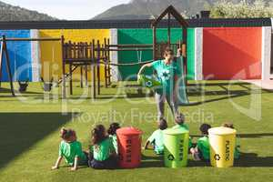 Teacher teaching about green energy and recycle in playground at schoolyard