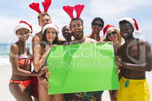 Multi-ethnic group of friends holding a empty green placard at beach on a sunny day