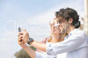 Caucasian couple taking selfie while standing at beach promenade