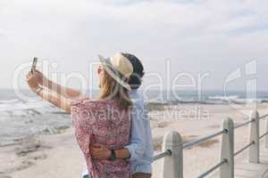 Caucasian couple taking selfie while standing near sea side at promenade