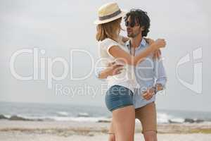 Caucasian couple looking at each other and dancing on beach