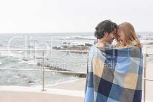 Caucasian couple wrapped in blanket standing at promenade near beach