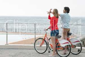 Caucasian couple interacting with each other while holding bicycle at promenade