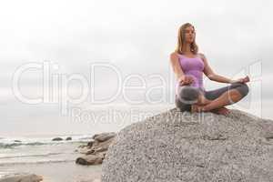 Caucasian woman perform yoga on the beach