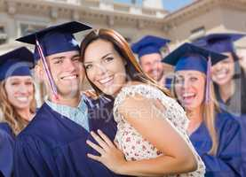 Proud Male Graduate In Cap and Gown with Girl Among Other Graduates