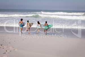 Group of friends with surfboard running towards sea at beach in the sunshine