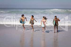 Group of friends with surfboard running at beach in the sunshine