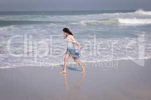 Young beautiful woman walking at beach in the sunshine