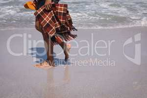 Man holding blanket and slipper while walking on beach in the sunshine