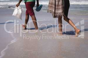Couple walking on beach in the sunshine