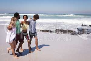 Happy group of friends walking on beach with arms around the waist