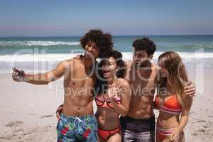 Group of friends taking selfie with mobile phone at beach in the sunshine