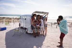 Man capturing photos of his friends sitting in the trunk of a camper van