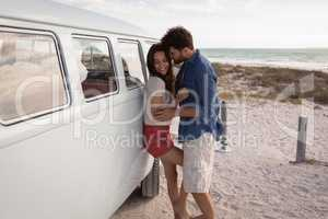 Side view of a Caucasian couple leaned on a camper van while they hugging themselves against ocean i