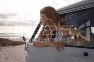 Side view of a Caucasian woman in a camper van with his head outside