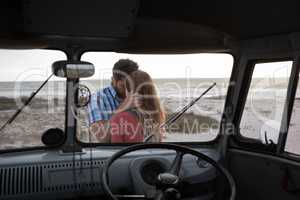 Inside view of a camper van of a Caucasian couple hugging each other against ocean in background