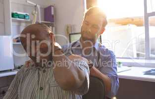 Caucasian male doctor checking neck of a senior man in clinic
