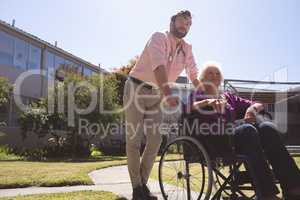 Male doctor caring disabled senior patient women in wheelchair