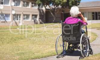 Senior woman relaxing on wheelchair at nursing home park