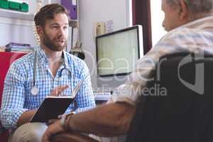 Male doctor prescribing medicament  to senior man in clinic