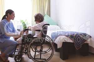 Nurse talking with senior female patient at nursing home
