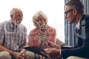 Male physician interacting with senior couple at retirement home