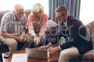 Matured male physician and senior couple discussing over laptop at retirement home