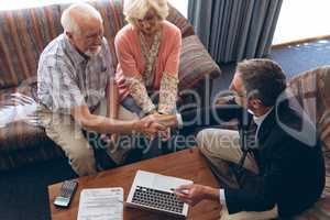 Male physician and senior couple discussing over laptop