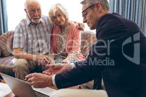 Male physician discussing over the laptop with senior couple at retirement home