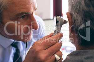 Male doctor checking senior female patient in clinic