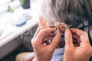 Male doctor applying hearing aid to senior woman