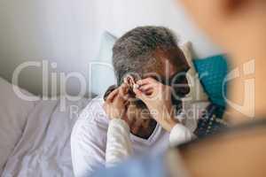 Female doctor applying hearing aid to senior man ear