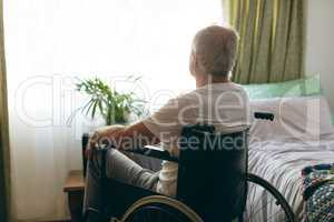 Male patient  looking outside the window while sitting in wheelchair
