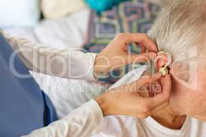 Female nurse applying hearing aid to senior male patient ear