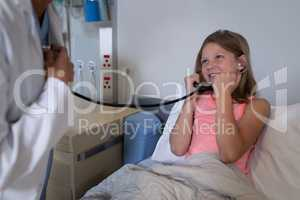 Girl patient listening to doctors heart beat with stethoscope
