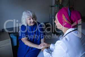 Mature female doctor talking with senior patient in hospital room