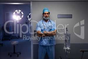 Male surgeon standing outside the operation room at hospital
